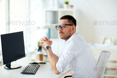 businessman in glasses sitting at office computer