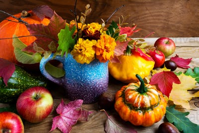 Rustic fall  table centerpiece with pumpkins and leaves, close u