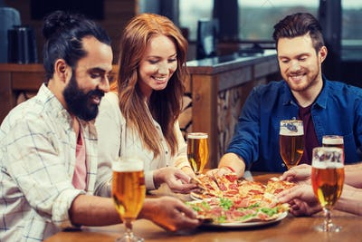 friends eating pizza with beer at restaurant