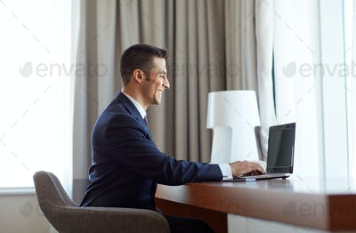 businessman typing on laptop at hotel room