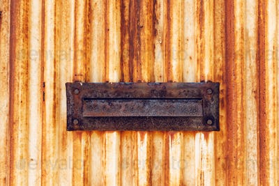 Weathered old rusty mail slot letterbox