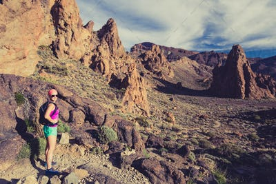 Happy girl hiker walking on mountain path, backpacker adventure