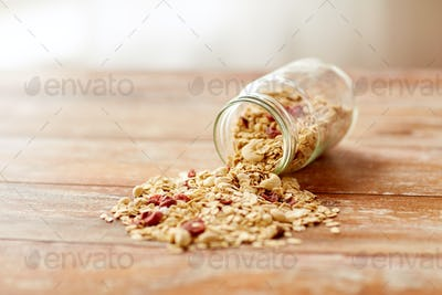 jar with granola or muesli poured on table