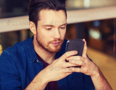 man with smartphone reading message at restaurant