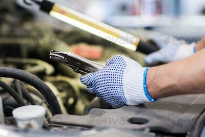mechanic man with pliers repairing car at workshop