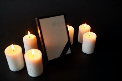 photo frame with black mourning ribbon and candles