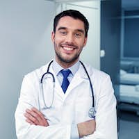 smiling doctor with stethoscope at hospital