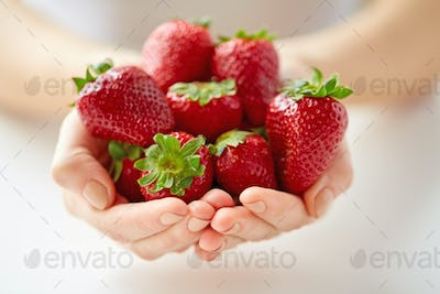close up of young woman hands holding strawberries