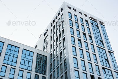 Transparent walls with small ajar windows reflecting bright blue sky