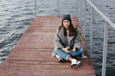 Young pretty girl on wooden bench on old pier