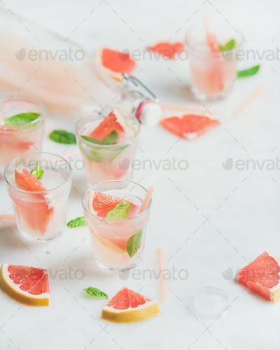 Cold refreshing alcohol cocktail with fresh grapefruit, white background