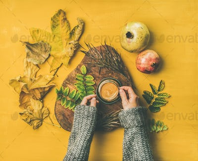 Woman' s hands in grey woolen sweater holding cup of espresso