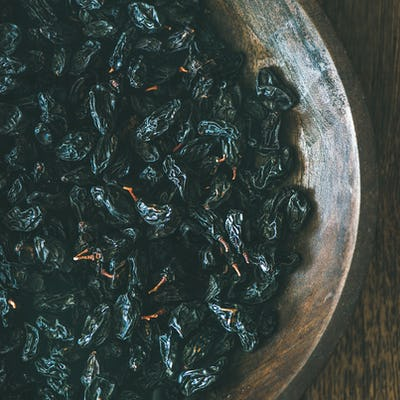 Black dried raisins in plate over wooden background, square crop