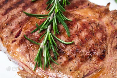Delicious beef steak with rosemary bunch.