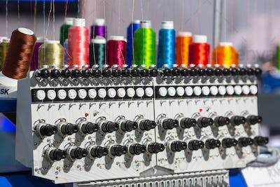 Spools of color threads closeup, spinning machine