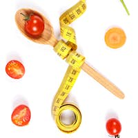 Spoon with centimeter and vegetables, slimming and healthy nutrition concept