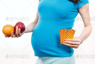 Pregnant woman holding fresh ripe fruits and medical pills or supplements