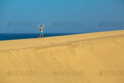 Woman with arms up raised on sand desert dunes