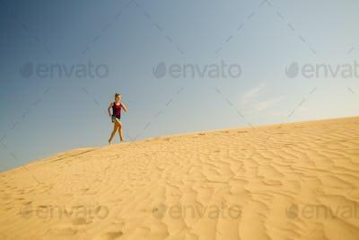 Young woman running on sand desert dunes
