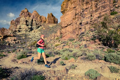 Young woman running in inspirational mountains landscape