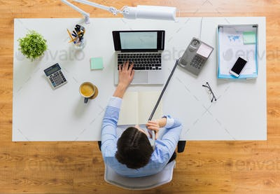 businesswoman calling on phone at office table