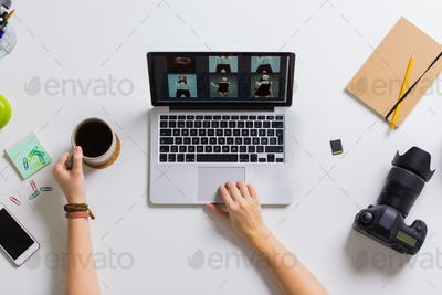 woman hands with camera working on laptop at table