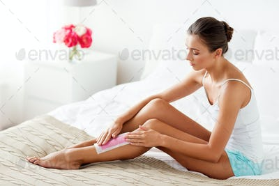 woman epilating leg hair with wax strip at home