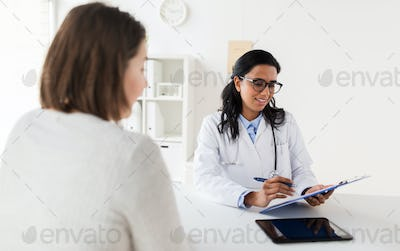 doctor with clipboard and woman patient at clinic