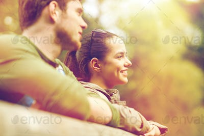 smiling couple with backpacks on bridge in nature