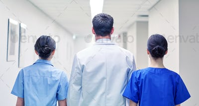 group of medics or doctors walking along hospital
