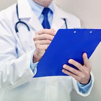 close up of doctor with clipboard at hospital