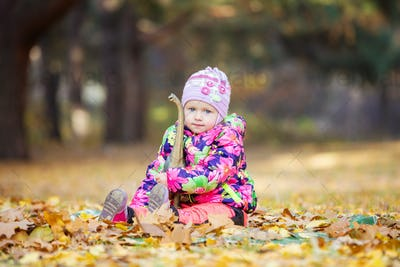 Little girl playing with toy dinosaur outdoors