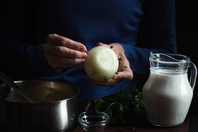Large onion in hands, jug with milk on a blue background