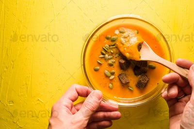 Pumpkin soup with seeds and croutons on a yellow table and spoon in hand