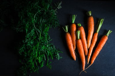 Whole green tops and carrots on a blue stone