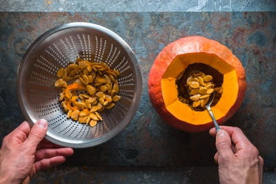 Hands hold a colander and a spoon in the pumpkin
