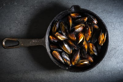 Mussels on a cast-iron frying pan on a gray background