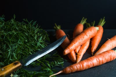 Orange carrots, leaves and a knife on a dark blue background