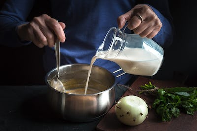 Milk from the jug is poured into a base sauce for making bechamel
