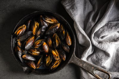 Mussels on a cast-iron frying pan and napkin on a gray background diagonal