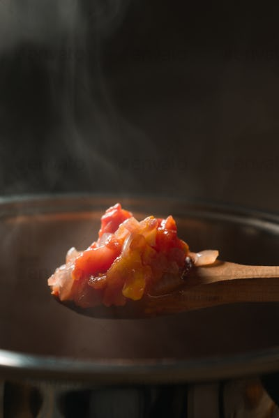 Wooden spoon with tomato and pumpkin over the pan