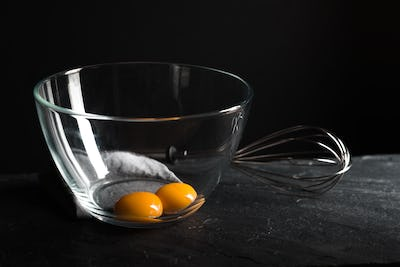 Chicken yolks in a bowl and whisk for beating on a gray table