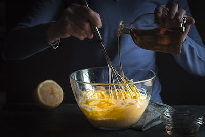 Beat egg yolks with mustard and olive oil