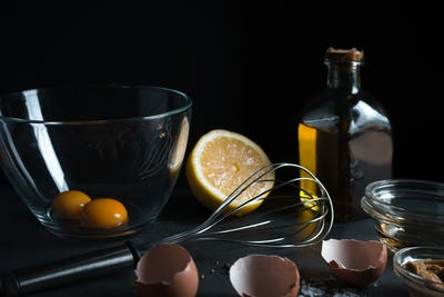 Yolks in a bowl, whisk for whipping, mustard and olive oil side view