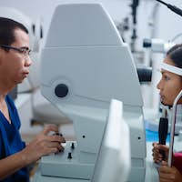 Eyesight exam in clinic with Asian doctor and female patient