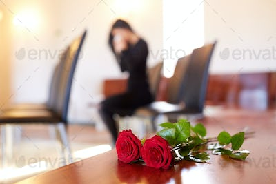red roses and woman crying at funeral in church