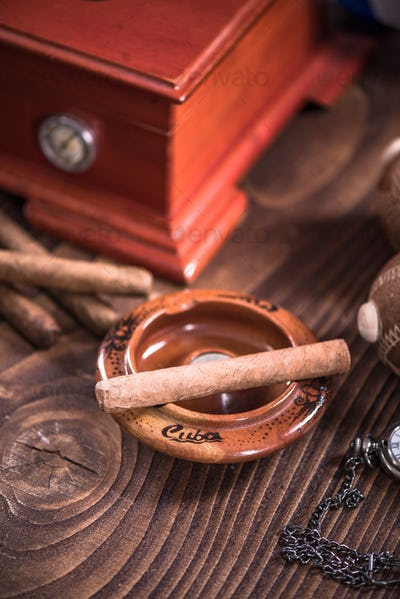 Cuban cigar in ashtray on wooden table