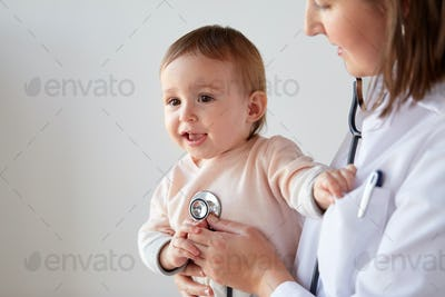 doctor with stethoscope listening baby at clinic