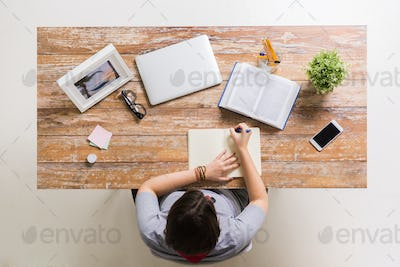woman with book writing to notebook at table