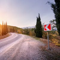 Beautiful asphalt road with road sign in mountains at sunset